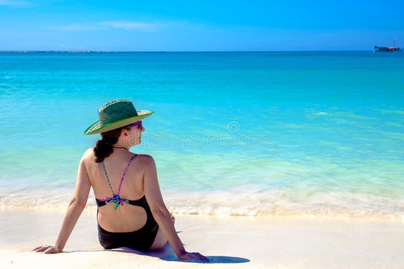 Vuxen kvinna som tar i strandsolen arkivfoto