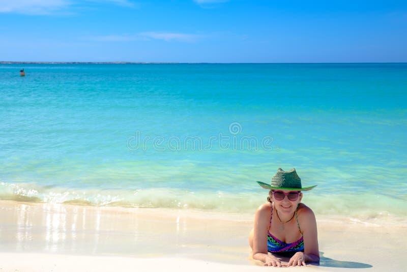 Vuxen kvinna som tar i strandsolen royaltyfri bild