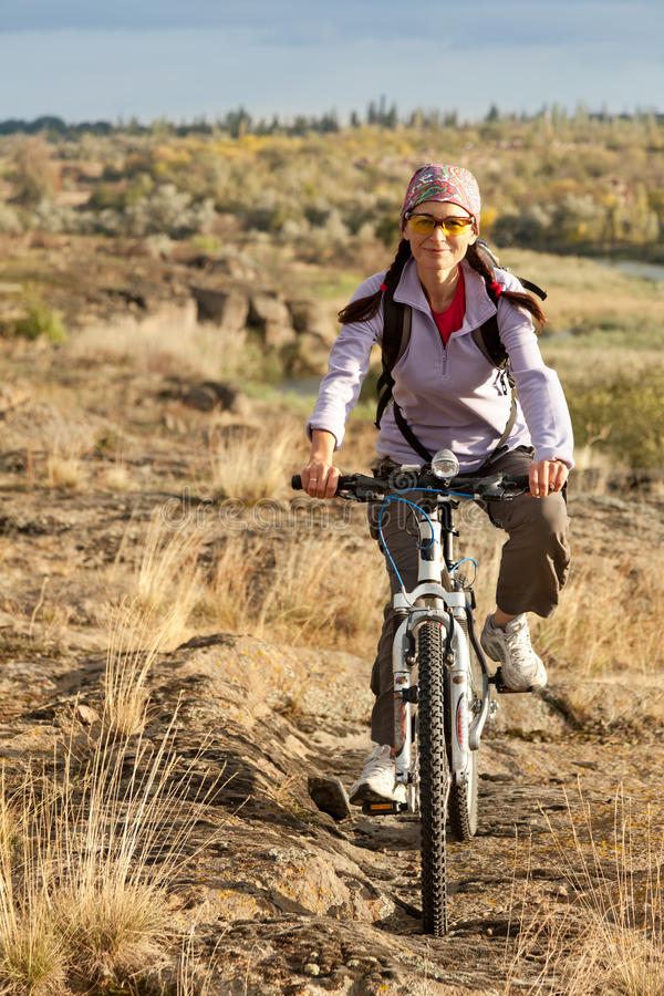 Vuxen kvinna som trampar på en mountainbike arkivbilder