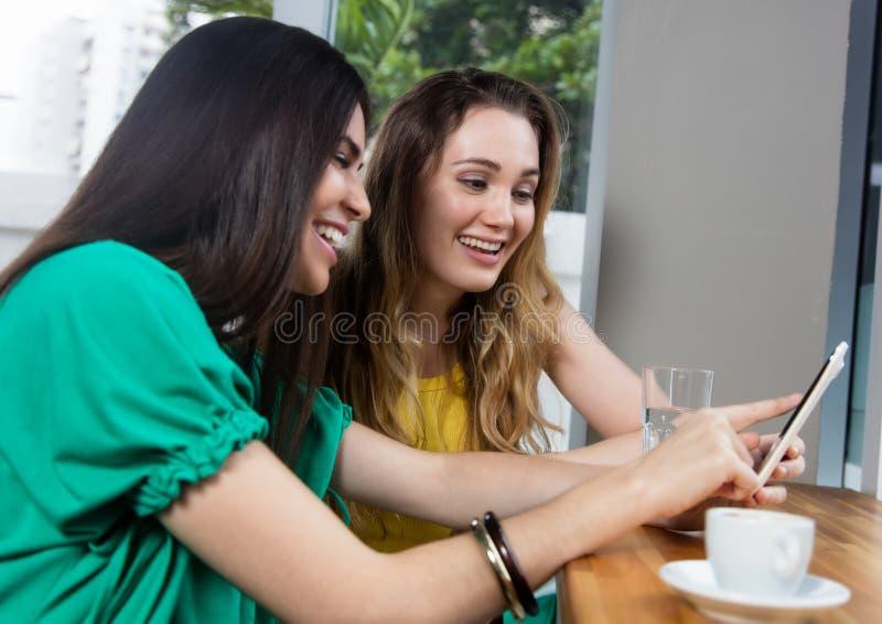 Vuxen kvinna som två ser bilder på en telefon arkivfoton