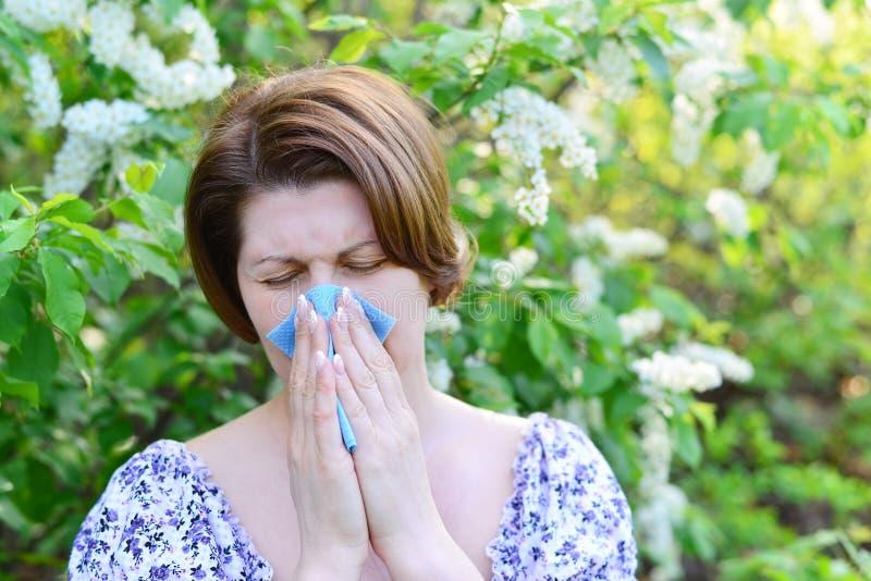 Vuxen kvinnlig med allergisk rhinitis om häggblomningar fotografering för bildbyråer