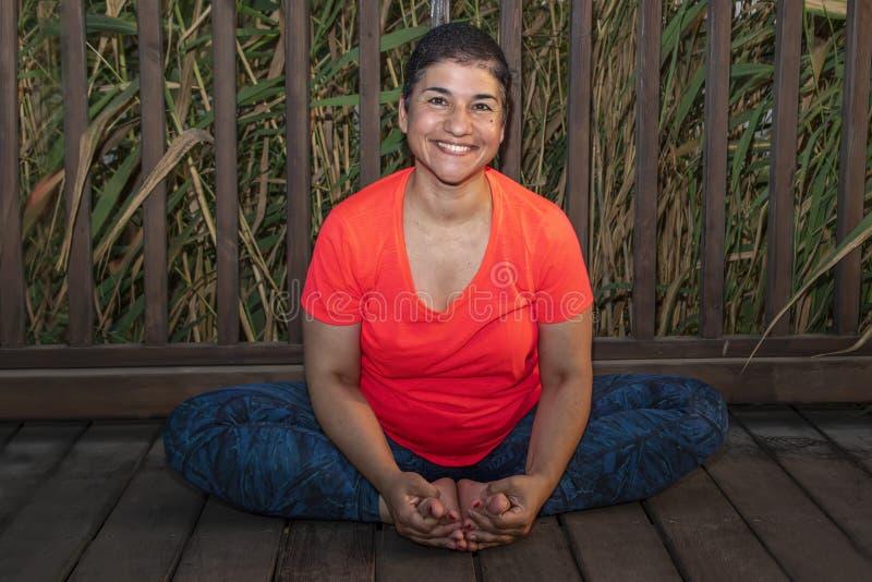 Vuxen le kvinna som utomhus gör yoga för att koppla av hennes mening och för att få i handlag med hennes anda royaltyfri foto
