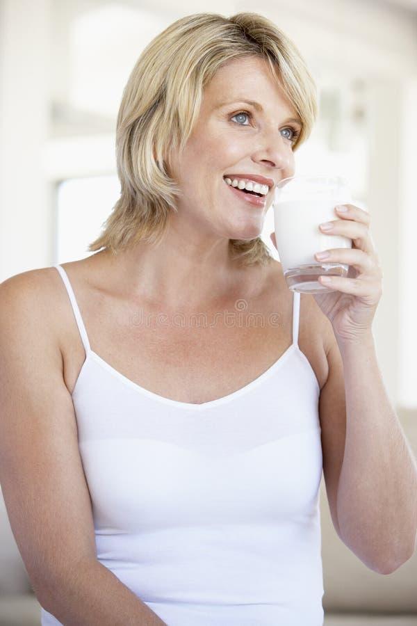 vuxen människa som dricker glass mitt-, mjölkar kvinnan royaltyfria bilder