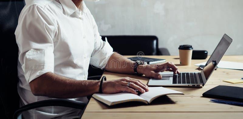 Vuxen människa uppsökt affärsman som bär klassiskt exponeringsglas och arbete på den wood tabellen i modern vind Stilfull mellers arkivbilder
