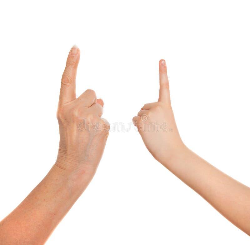 Vuxen människas hand och barns hand som pekar upp arkivfoton