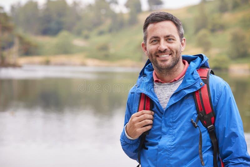 Vuxen man på ett anseende för campa ferie vid en sjö som ler till kameran, stående, sjöområde, UK arkivfoton
