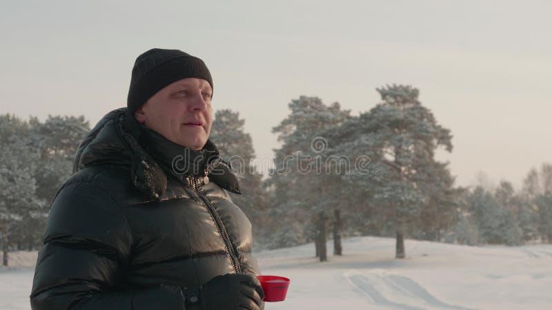 Vuxen man som dricker varmt te på snöig skoglandskap på kopieringsutrymme på vinterdagen arkivbilder