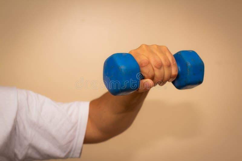Vuxen man som gör övning i idrottshallen Man med små blåa vikter H?lso- och wellnessbegrepp arkivbild