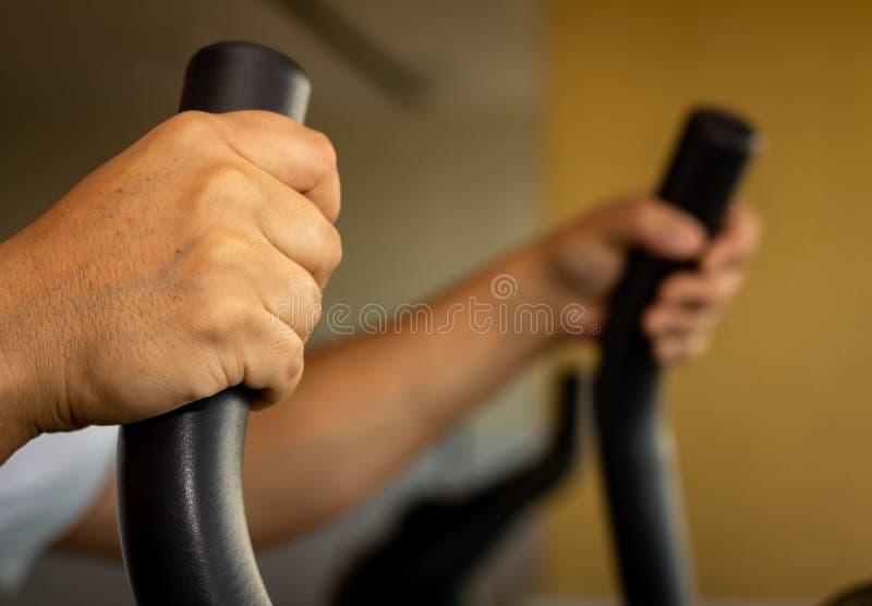 Vuxen man som g?r ?vning i idrottshallen I maskinen som gör aerobisk övning arkivfoton