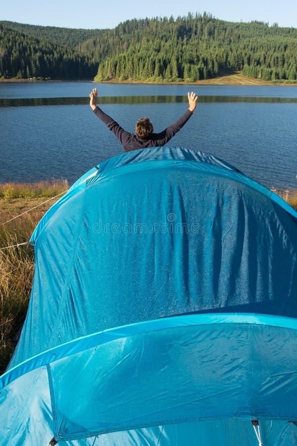 Vuxen man som tycker om naturmorgon, då gå ut ur tältet arkivbilder