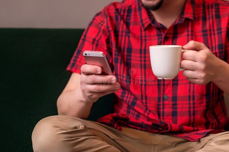 Vuxen manläsning eller hålla ögonen på något på smartphonen som sitter på soffan med en kopp Nöjd förbrukning och förbindelselivb royaltyfri bild