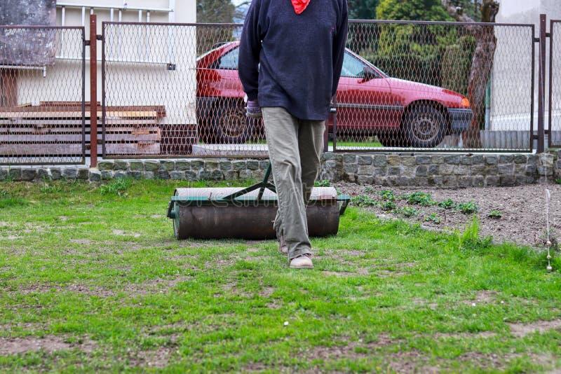 Vuxen manlig landskap trädgård efter lång vinter V?rarbete Utslätn av gräsyttersida i trädgården ut Hård och ansträngande trädgår arkivbilder