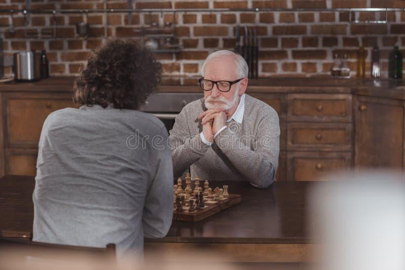 vuxen son och hög fader som tänker, medan spela schack arkivfoton