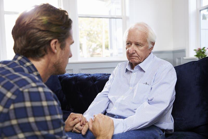 Vuxen son som talar till den deprimerade fadern At Home royaltyfria bilder