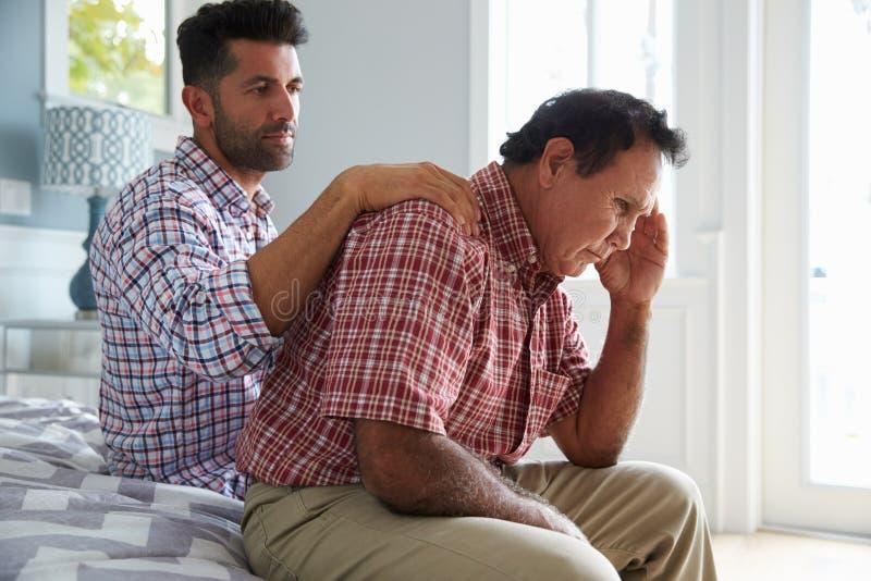 Vuxen son som tröstar fadern Suffering With Dementia royaltyfria foton