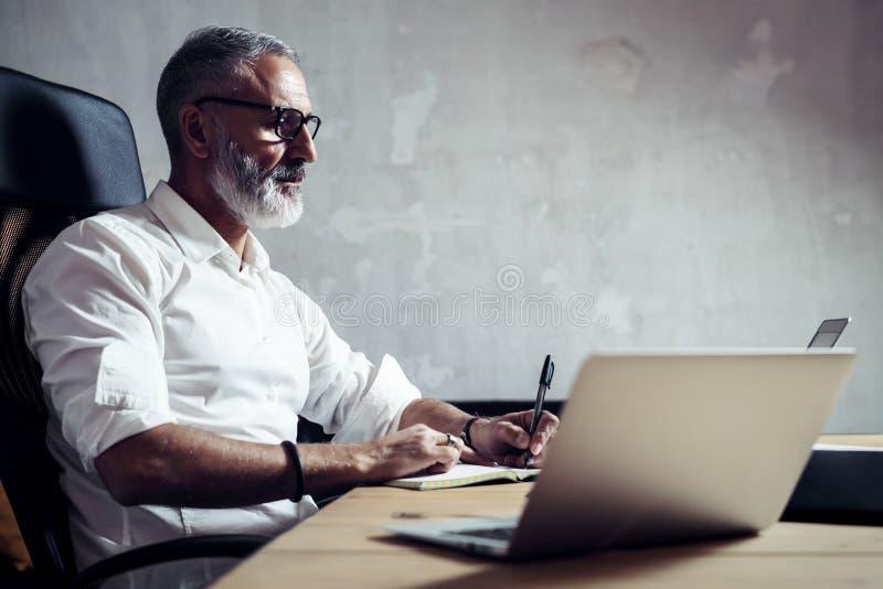 Vuxen stilfull affärsman som bär klassiskt exponeringsglas och arbete på den wood tabellen i modern vind Elegant mandanande arkivbilder