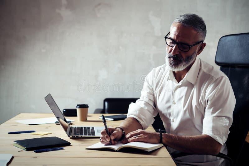 Vuxen stilfull affärsman som bär klassiskt exponeringsglas och arbete på den wood tabellen i modern vindstudio Skäggig mitt royaltyfri fotografi