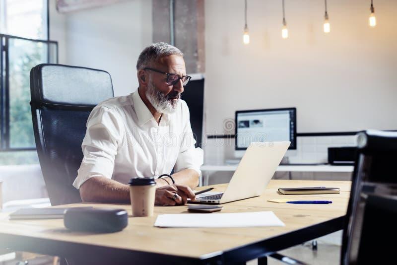 Vuxen yrkesmässig affärsman som bär klassiskt exponeringsglas och arbete på den wood tabellen i modern coworking studio fotografering för bildbyråer