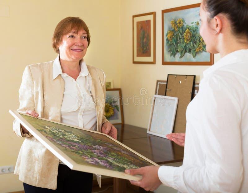 Vuxna kvinnlig som ser bilden i konstgalleri arkivbild