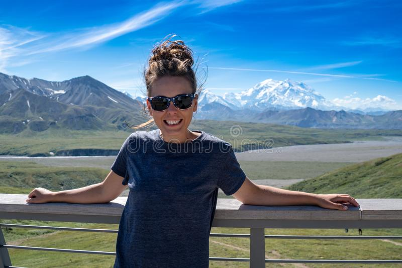 Vuxna kvinnliga ställningar som är främsta av Denali berg i det Alaska området arkivbilder