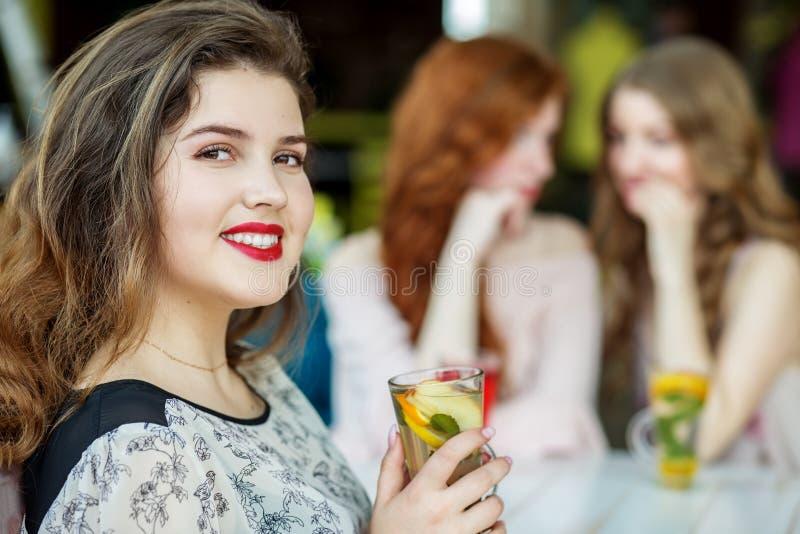 Vuxna kvinnor skvallrar bak baksidan av en v?n Begreppet av livsstilen, skvaller, l?gner, kamratskap royaltyfri foto