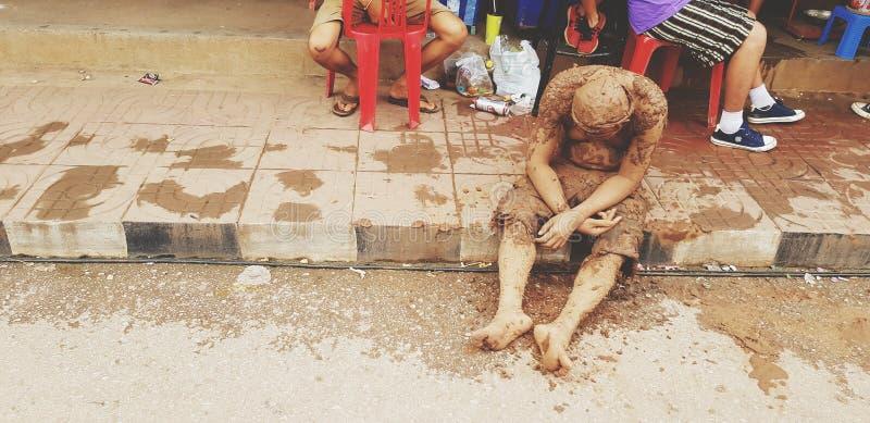 Vuxna människan eller gamala mannen befläckte gyttjan som sitter och sovande på vandringsledblicken som full man för folk royaltyfri bild