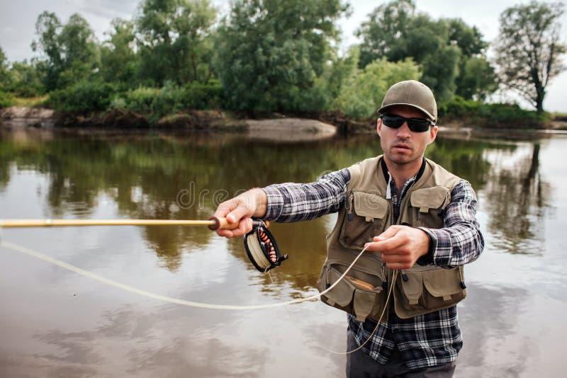 Vuxna människan med solglasögon står i rättframt vatten- och innehavfluga-fiske Det finns en del av skeden i annan royaltyfria foton