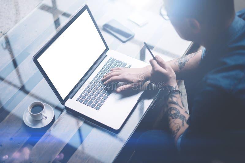 Vuxna människan tatuerade affärsmannen som arbetar på den mobila datoren på det soliga kontoret Affärsmanmaskinskrivning på antec fotografering för bildbyråer