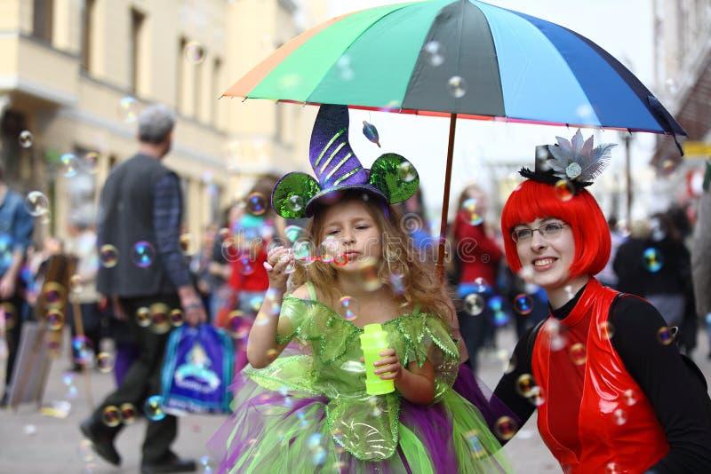 Vuxna människor och barn i maskeradkläderna som har gyckel arkivfoton