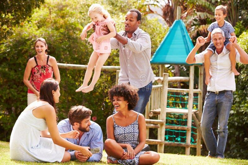 Vuxna människor och ungar som har gyckel i en trädgård arkivfoton