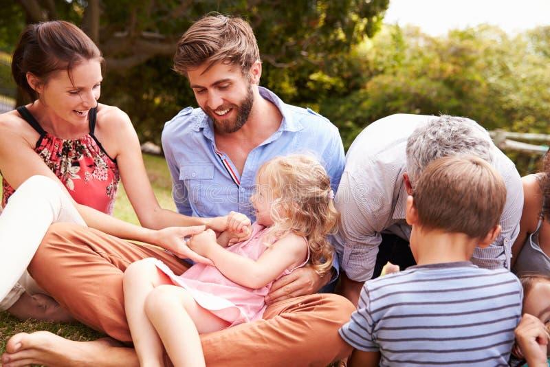 Vuxna människor och ungar som sitter på gräset i en trädgård arkivbild