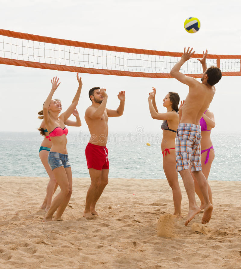 Vuxna människor som kastar bollen över netto och att skratta fotografering för bildbyråer
