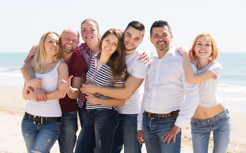 Vuxna människor som kopplar av på den sandiga stranden arkivfoto