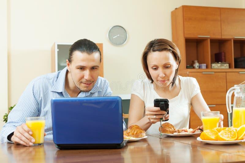 Vuxna par genom att använda elektroniska apparater under frukosten royaltyfri foto