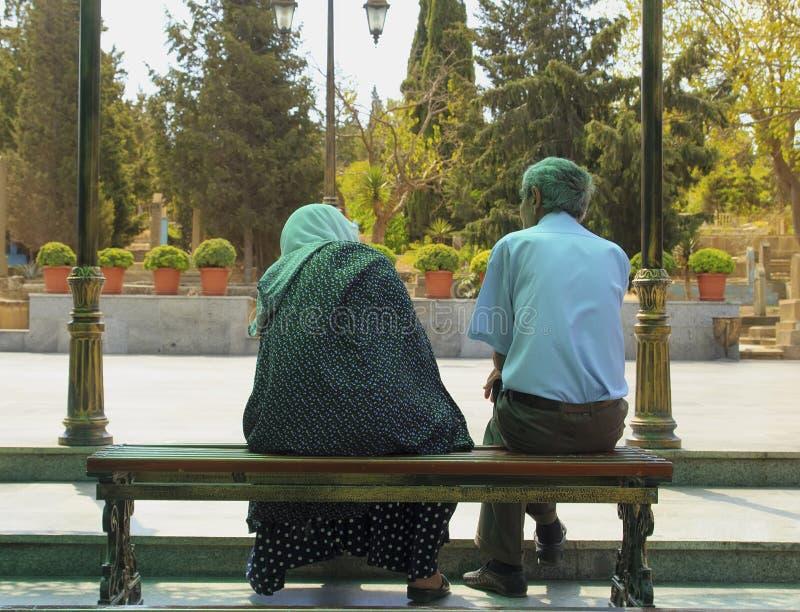 Vuxna par i sorg på bänken som tillbaka sitter royaltyfri foto