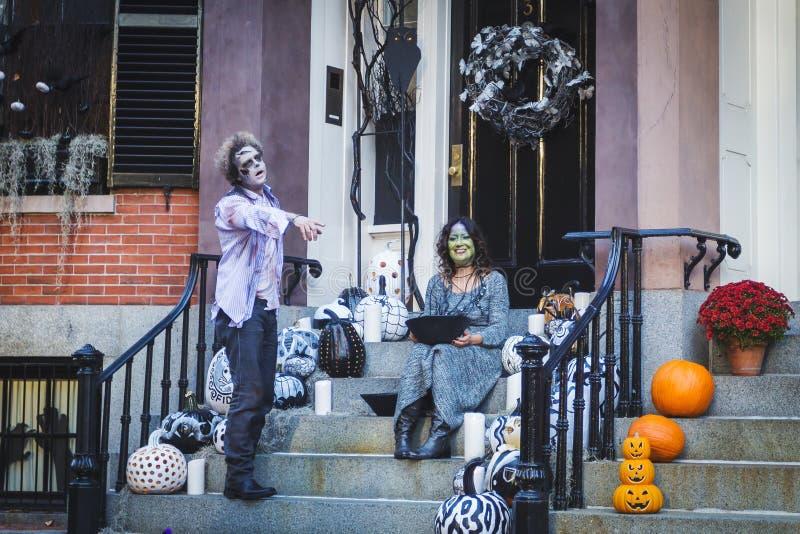 Vuxna par klädde som levande död och en häxa som poserar nära deras hus på allhelgonaafton royaltyfria foton