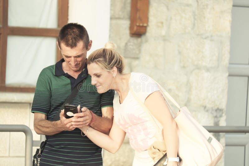 Vuxna par ser Smartphone, den Ostrog kloster - Monteneg arkivfoton