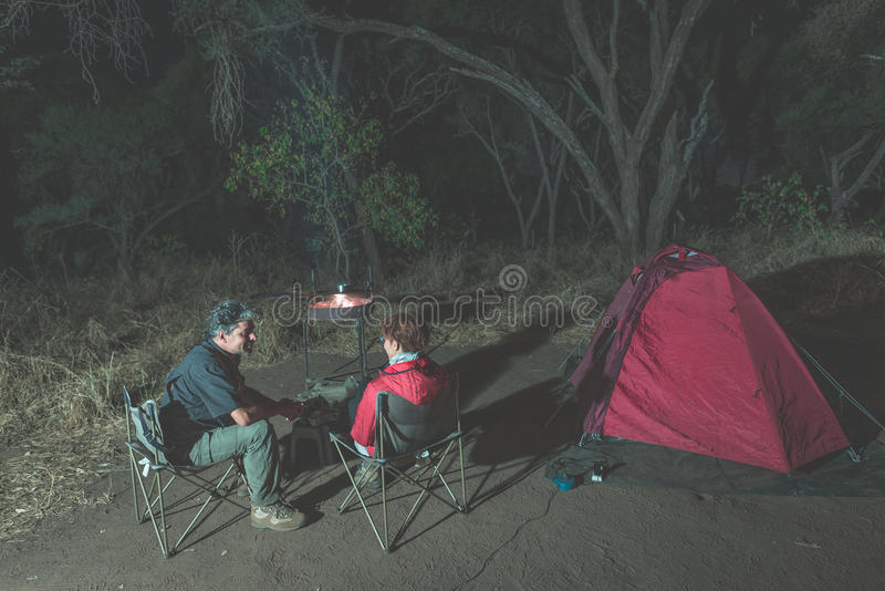 Vuxna par som kopplar av i campa plats vid natt Affärsföretag i nationalparken, Sydafrika Brinnande lägerbrand och tält i backgre fotografering för bildbyråer