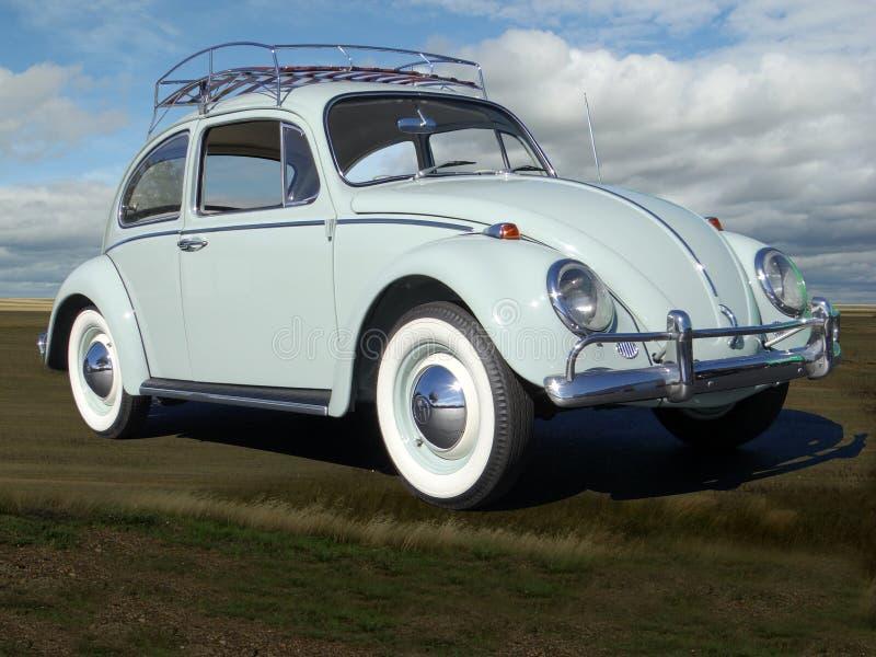 VW Käfer 1965 mit coluds im Himmel stockfotografie