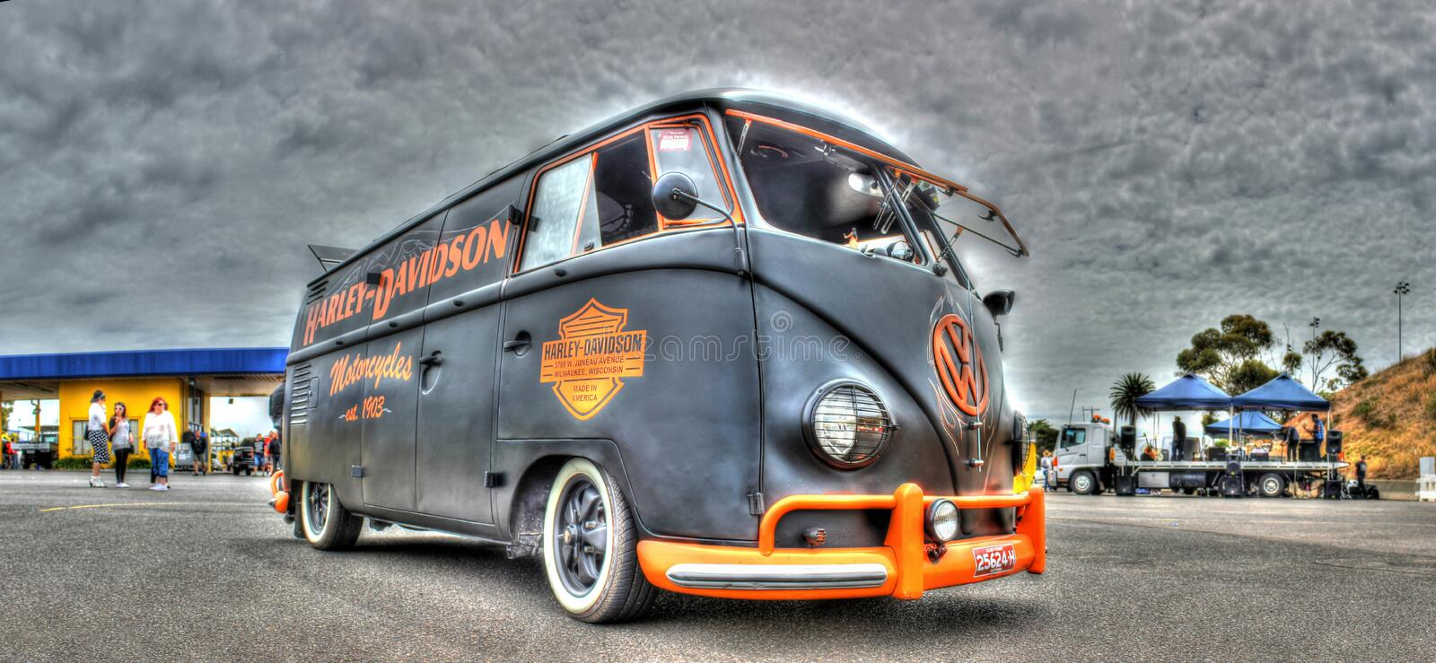 VW Kombi painted in Harley Davidson Colors. A custom painted VW Kombi in the black and orange colors of Harley Davidson motorcycles on display at car show held stock photos