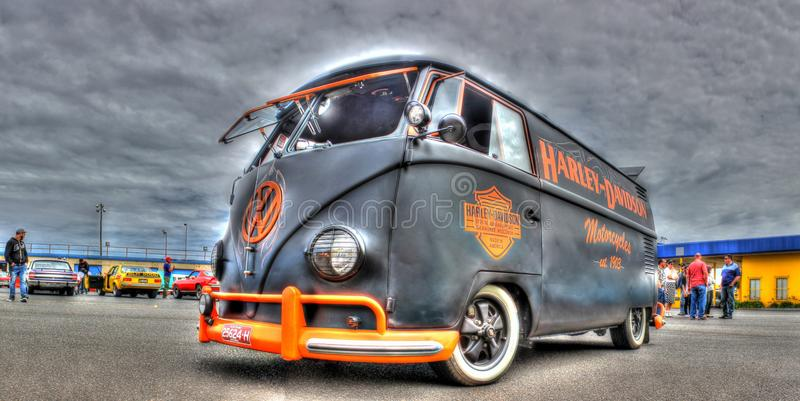 VW Kombi painted in Harley Davidson Colors. A custom painted VW Kombi in the black and orange colors of Harley Davidson motorcycles on display at car show held stock photography