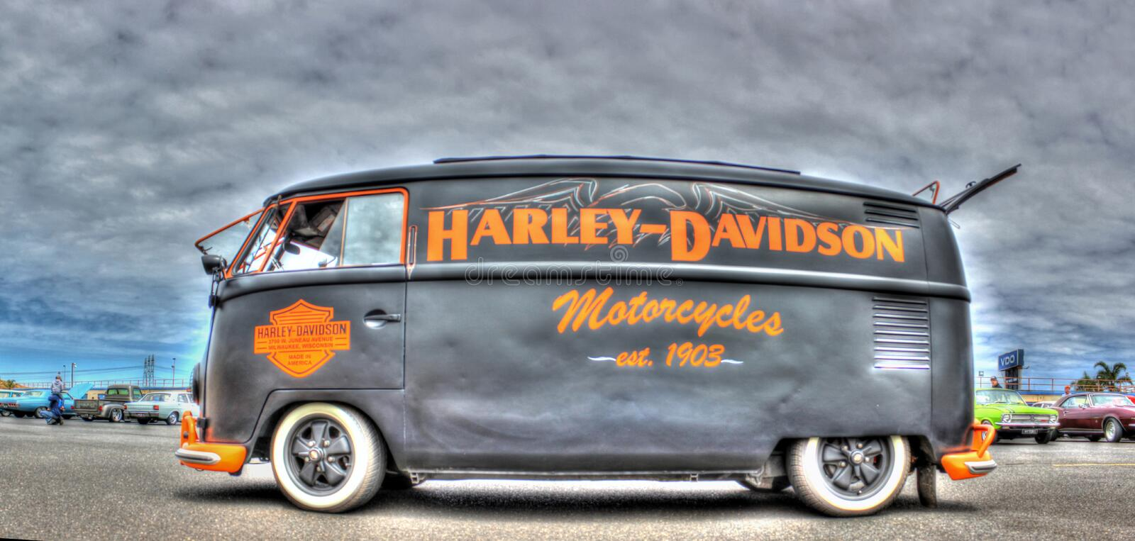 VW Kombi painted in Harley Davidson Colors. A custom painted VW Kombi in the black and orange colors of Harley Davidson motorcycles on display at car show held royalty free stock photo