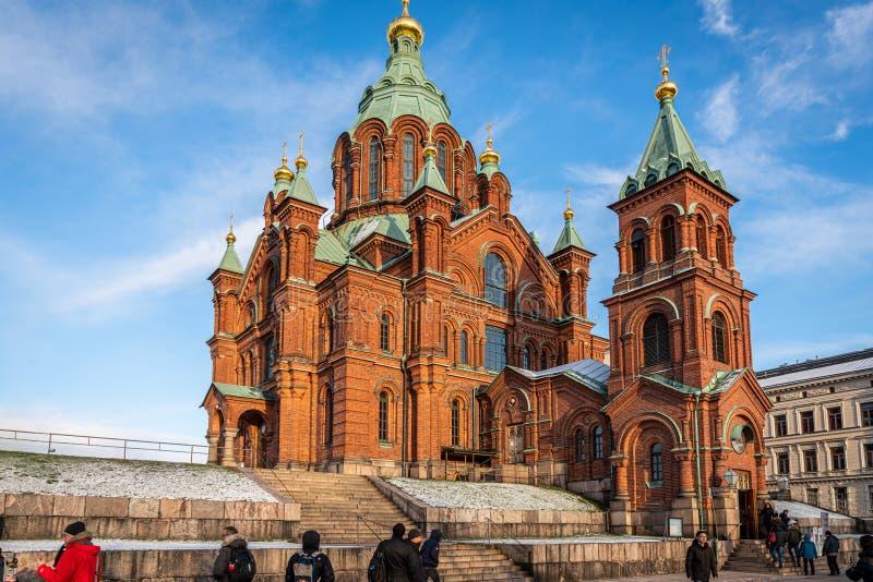 Vy över den berömda röda ortodoxa katedralen Uspenski med anhängare i förgrunden i Helsingfors royaltyfri foto