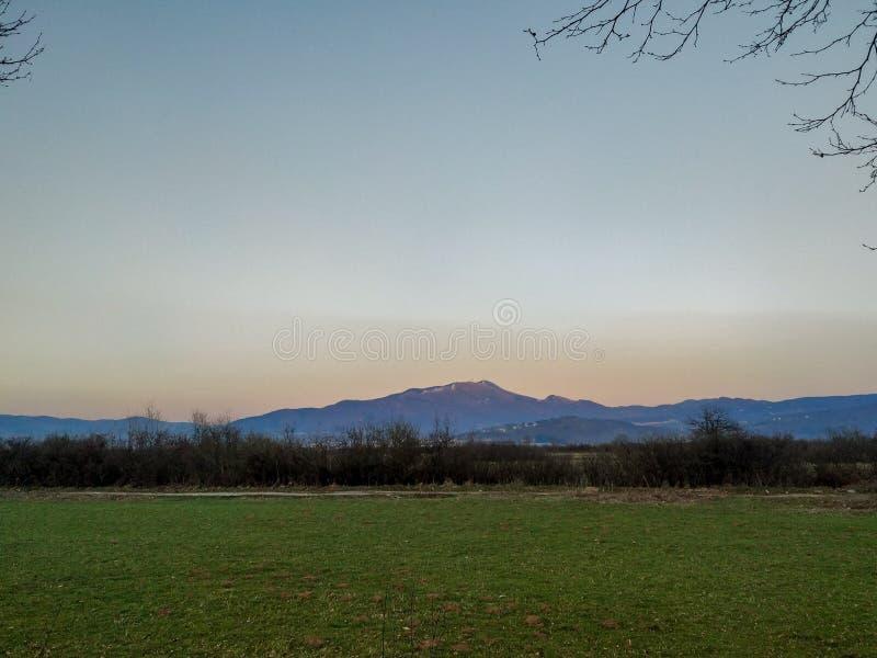 Vy över ett avlägset berg och grönområde på marken på en vacker solig dag kväll eller morgon i naturskrivbordsunderlägg royaltyfria foton