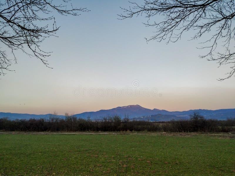 Vy över ett avlägset bergsområde och grönområde på marken omgivet av trädgrenar på en vacker solig dag kväll eller morgon arkivbild