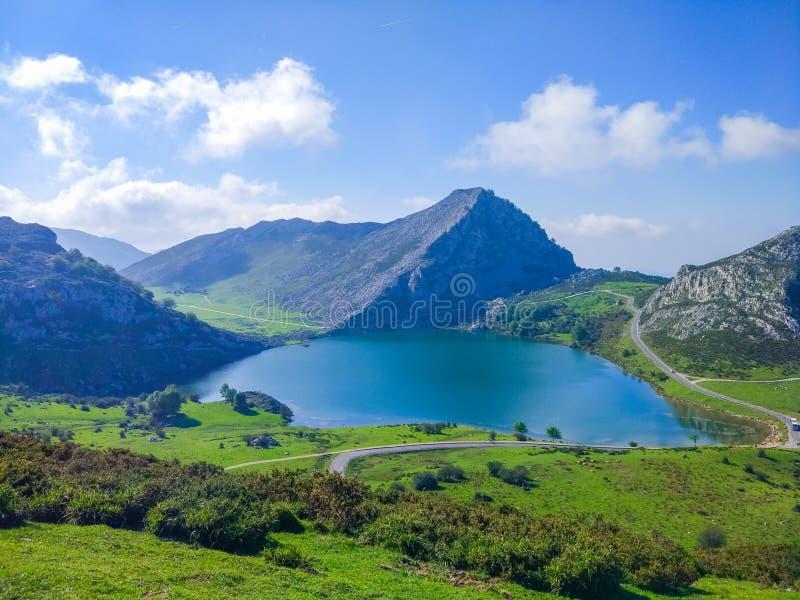 Vy över sjön Enol i sjöarna Covadonga, Asturien, Spanien, från utkik Grön gräsmark med berg i bakgrunden arkivbild