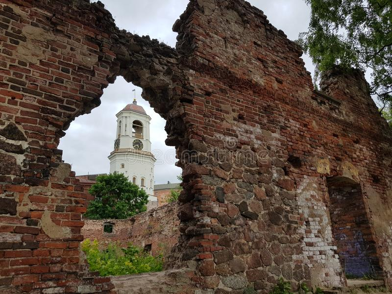 Vyborg Vista de la torre de reloj a través de la ventana de la casa destruida foto de archivo