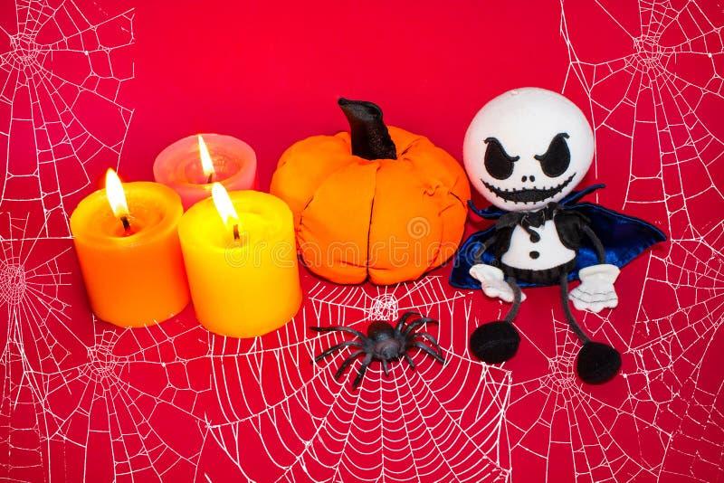 Vykort för allhelgonaaftonen, stearinljus med den pumpa-, spindel- och spökedockan På en röd bakgrund med en spindelnät royaltyfri bild