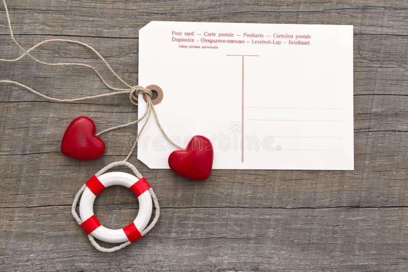Vykort för meddelande med två röda hjärtor och livboj på grå färger w royaltyfri bild