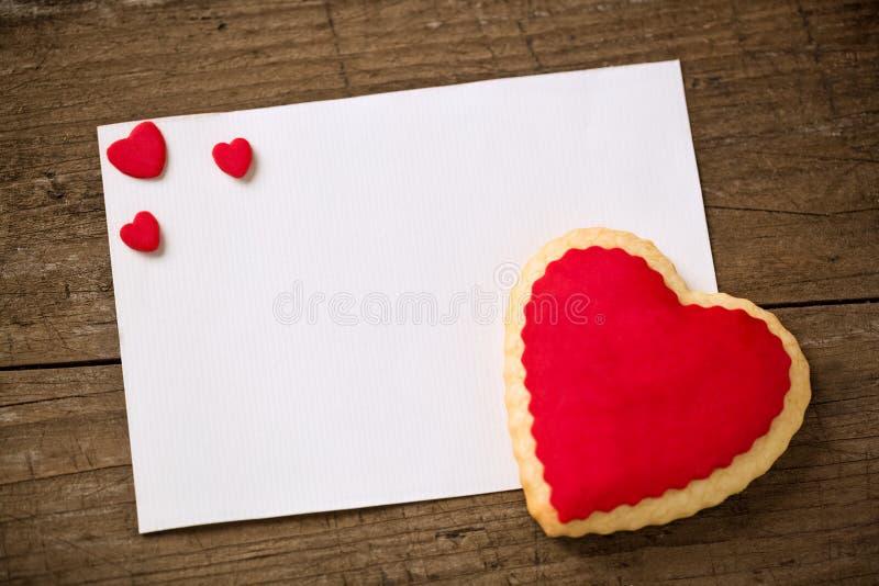 Vykort för valentin dag, kakahjärta på papper royaltyfri bild